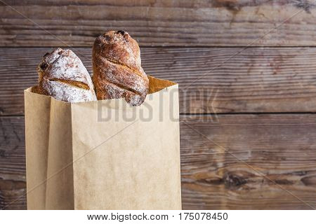 Fresh bread in a paper bag on a wooden table