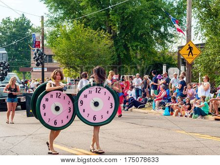 TWINSBURG OH USA - AUGUST 8 2015: Twin sisters dressed as pink clocks march in the Double Take Parade part of the 40th annual Twins Day festival the largest gathering of twins in the world.