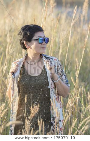 portrait of asian woman wearing sun glasses standing with relaxing post in beautiful grass field