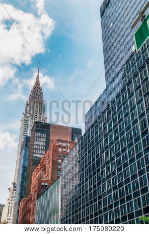 NEW YORK CITY, USA - AUGUST 8, 2016: Top of the Chrysler building with blue sky background. It is the tallest brick building in the world, with a steel structure.
