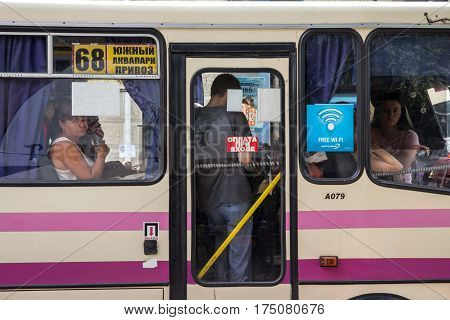 ODESSA UKRAINE - AUGUST 13 2015: Passengers looking out of the window of a marshrutka, a collective taxi/minibus operating urban routes in most of post soviet cities