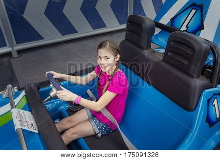 Child enjoying a day at an outdoor amusement park. Sitting in an automobile theme park ride ready to go on a warm summer day outdoors. Smiling and having fun and ready to go on a ride