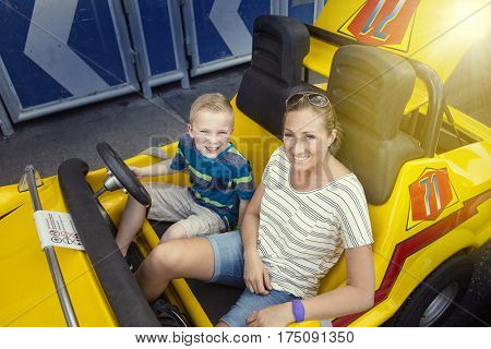 Family enjoying a day at the amusement park. Sitting in an automobile theme park ride ready to go on a warm summer day outdoors. Smiling and having fun together as a family