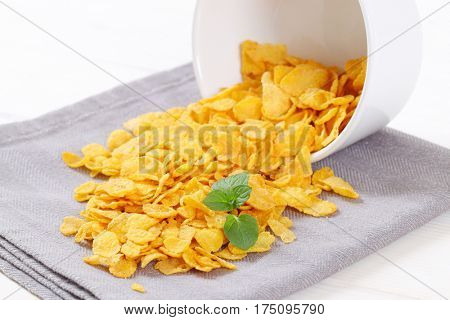 pile of corn flakes spilt out on grey place mat - close up