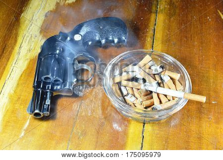 revolver gun and cigarette in glass ashtray on wooden table