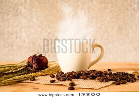 The Hot Coffee In The White Cup On Wooden Table With Coffee Seed