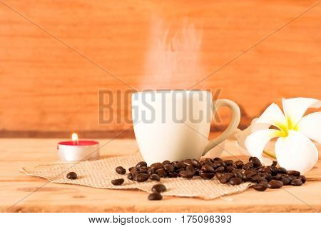 The Hot Coffee In The White Cup On Wooden Table With Coffee Seed And Red Candle