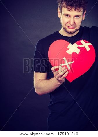 Bad relationships breaking up sadness emotions concept. Very sad young man holding broken heart made of paper.