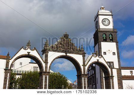 Portas da Cidade Gates and Saint Sabastian church with clock tower Ponta Delgada Portugal. Azores capital landmarks under cloudy skies.