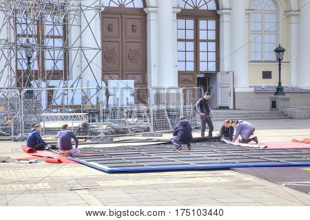 MOSCOW RUSSIA - April 24.2016: Brigade of workers collect enormous banner with a playbill to the future exhibition in Manege