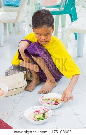 CHIANG RAI THAILAND - FEBRUARY 19 : Unidentified old asian woman suffering from leprosy eating food on February 19 2016 in Chiang rai Thailand.