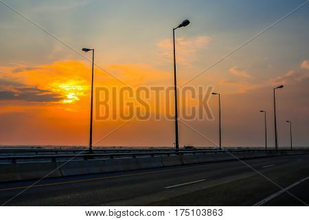 Lighting poles on the highway at sunset