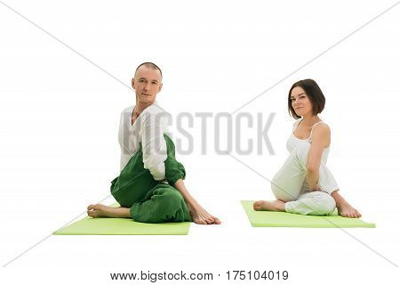 Couple in white sport tshirts and green trousers doing yoga exercises on green mats in studio isolated shot