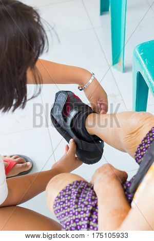 closeup young woman wearing shoe of old asian woman suffering from leprosy
