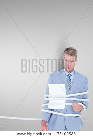 Businessman tied up in rope against grey background