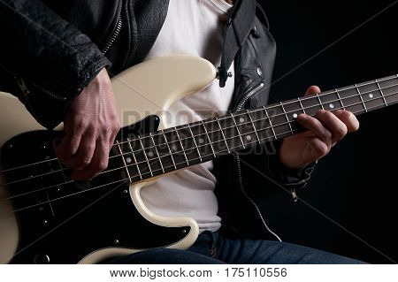 Rockstar in biker leather jacket playing solo on bass guitar.