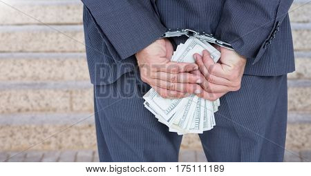 Businessman hands in handcuffs holding US dollars against blurr background