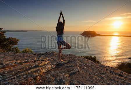 A woman standing on a rock looking out to the sea at sunrise doing tree pose variation yoga meditation Vrksasana