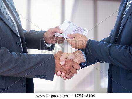 Businessman bribing partner while shaking hands against blurr background