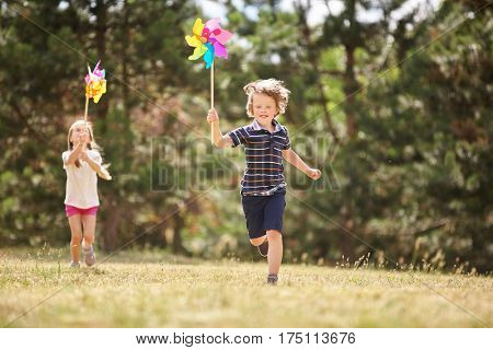 Girl and boy with pinwheels running and having fun