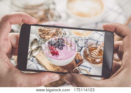 Taking photos of breakfast to phone. Social media concept. Sharing healthy food photos. Toned