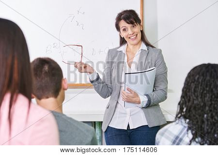 Teacher in front of her math class explains to her students