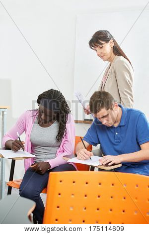 Students taking a test supervised by their teacher