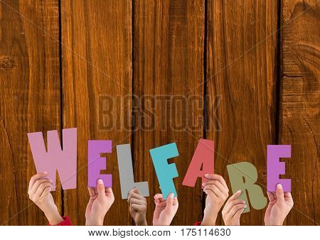 Composite image of hands holding word Welfare against wooden background