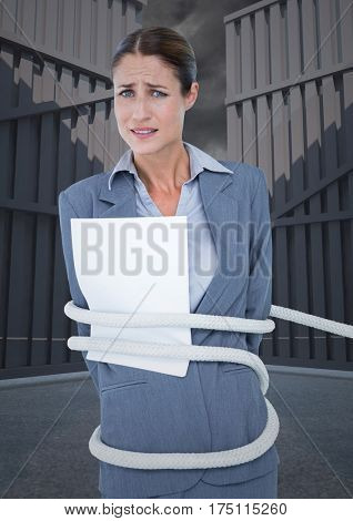 Digital composite image of tense businesswoman tied up with rope and paper