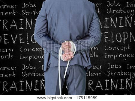 Rear view of businessman with his hands tied with rope against business terms in background