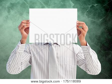 Digital composition of businessman holding blank placard in front of his face against green background