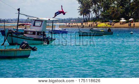 Menino pulando de um barco no mar
