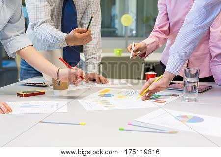 Business Team networking Concept - grey Office Table with many printed professional Paper Charts and Hands of People discussing gesturing pointing