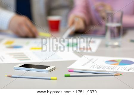 Solving Business Issue Concept - grey Office Table with Color professional Charts on Papers Pencils and Electronic Gadgets blurred Body of Businesspeople on Background