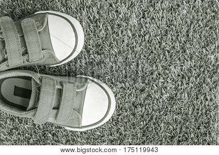 Closeup fabric sneakers of kid on gray carpet textured background in top view in black and white tone with copy space