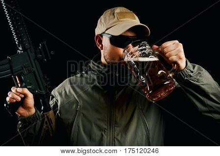 man in a cap with an assault rifle drinking beer
