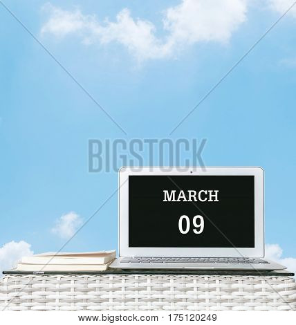 Closeup computer laptop with march 9 word on the center of screen in calendar concept on blurred wood weave table and book on blue sky with cloud textured background with copy space