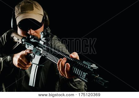 man in cap and jacket keeps assault rifle