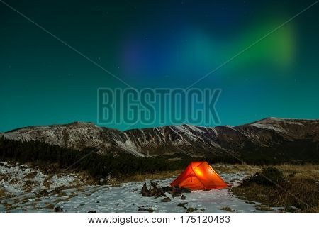 Polar Night landscape with illuminated tent and Polar Lights, Silhouettes of snowy mountain peaks night sky with many stars and Northern Lights on background illuminated orange tent on foreground