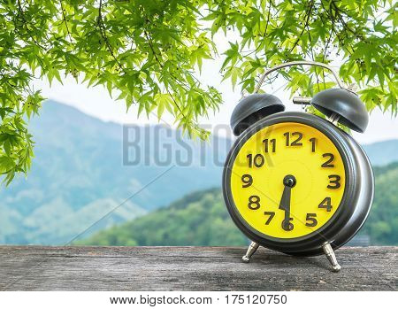 Closeup black and yellow alarm clock for decorate show half past six or 6:30 a.m. on blurred leaves and mountain view background
