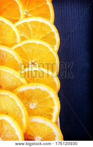 Juicy orange slices on navy blue board
