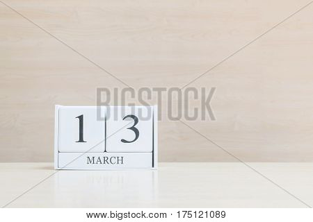 Closeup surface white wooden calendar with black 13 march word on blurred brown wood desk and wood wall textured background with copy space selective focus at the calendar