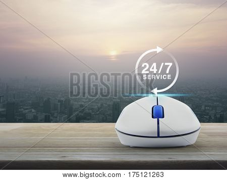 24 hours service icon with wireless computer mouse on wooden table over modern city tower at sunset vintage style Full time service concept