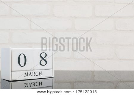 Closeup white wooden calendar with black 8 march word on black glass table and white brick wall textured background with copy space selective focus at the calendar