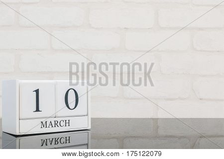 Closeup white wooden calendar with black 10 march word on black glass table and white brick wall textured background with copy space selective focus at the calendar