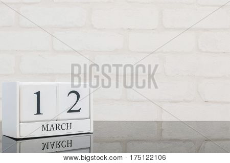 Closeup white wooden calendar with black 12 march word on black glass table and white brick wall textured background with copy space selective focus at the calendar