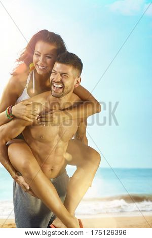 Happy loving couple having summer fun on the beach piggyback.