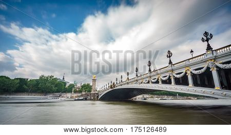 Long exposure silk water and wide angle view of Alexandre III Bridge, Paris France