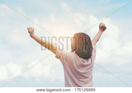 Relaxation Hapiness concept. Woman standing and feel freedom with arms stretched on blue sky background.
