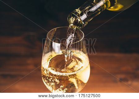 Pouring White Wine From A Bottle In A Close Up View Of The Wineglasses Against Wooden Background
